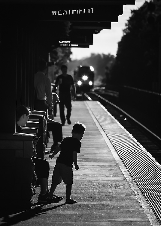 A Westbound commuter train approaches Westfield, Nj as a young boy watches the approach.