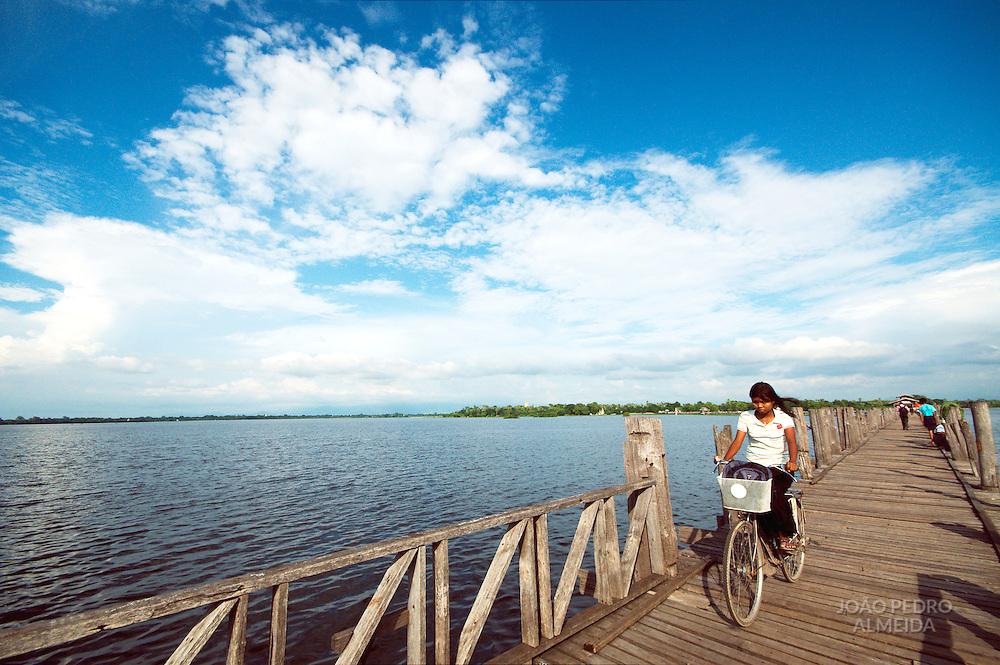 Girl riding a bike across U Bein bridge