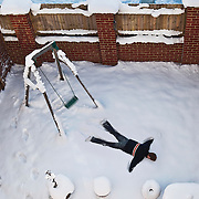A humorous photographer showing a man, face down in the snow having jumped from a swing in his garden.