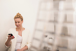 Mid adult woman text messaging on smart phone, Munich, Bavaria, Germany