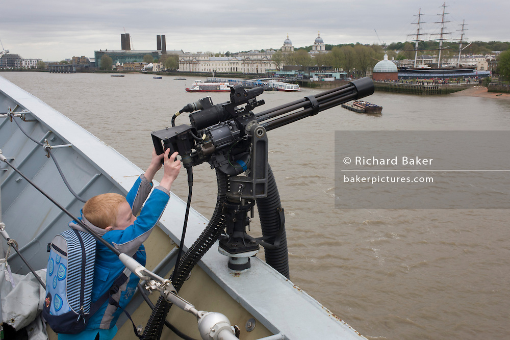 A young boy, too short to reach points a Minigun cannon from the top deck of HMS Illustrious over the river Thames at Greenwich, London. During which the Royal Navy's aircraft carrier was docked on the river, allowing the tax-paying public to tour its decks before its decommisioning. Navy personnel helped with the PR event over the May weekend, historically the home of Britain's naval fleet.
