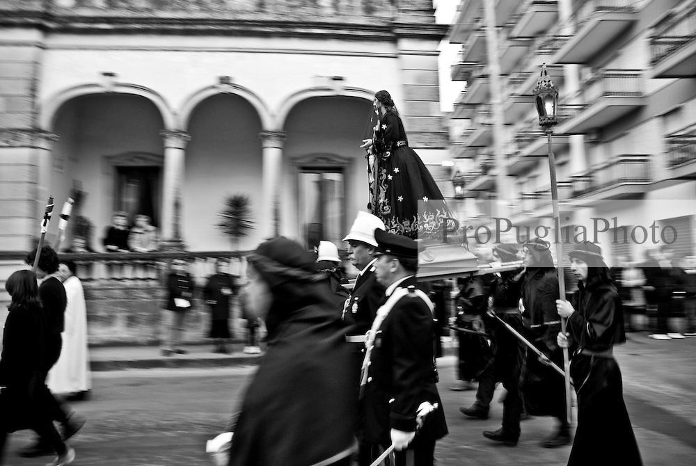 """La sttua della Desolata portata a spalla da quattro uomini e """"scortata"""" da appartenenti alle forze dell'ordine"""