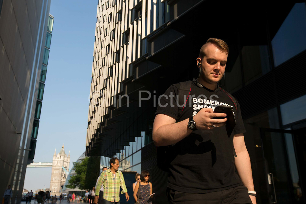 A Pedestrian checks his mobile phone while walking near London Bridge on 19th June 2017 in London, United Kingdom.  From the series Our Small World, an observation of our mobile phone obsessions