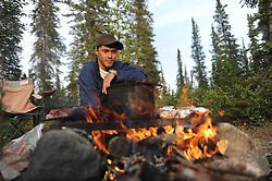 Damian Kailek, 24,  cooks fish in his home of Lutsel Ke' (aka Snowdrift) July 21, 2011 in the Northwest Territories of Canada.