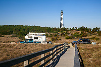 NC00891-00...NORTH CAROLINA - Cars passing Cape Lookout Lighthouse on the sand road through the dunes of the Core Banks in Cape Lookout National Seashore.