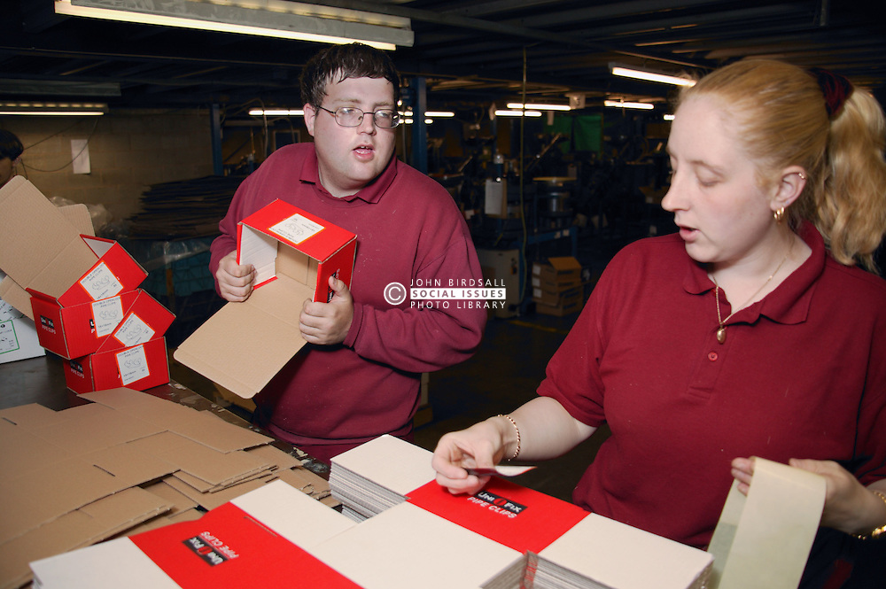 Man with learning disability and colleague working in factory assembling cardboard boxes,