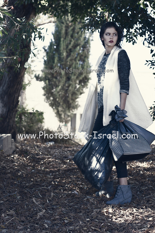 Homeless concept. Hip female model in fashionable clothes in a homeless looking environment