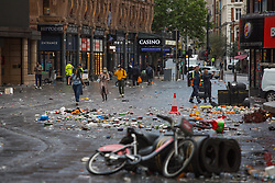 © Licensed to London News Pictures.  12/07/2021. London, UK. Members of the public commute through Leicester Square as piles of rubbish left behind football supporters in central London. England lost to Italy on penalties during yesterday's EURO 2020 final. Photo credit: Marcin Nowak/LNP
