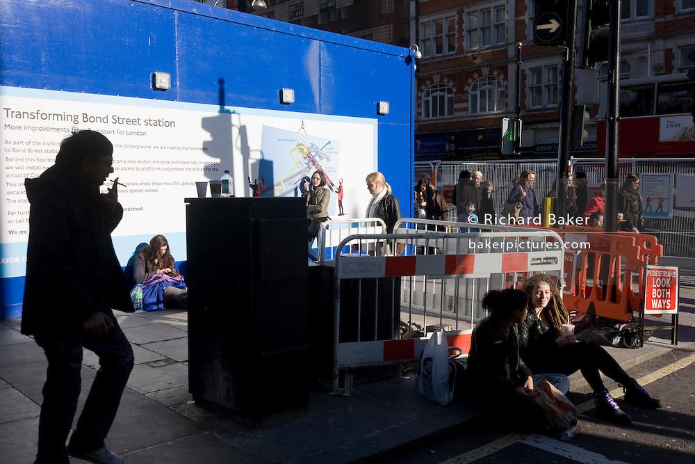 A city smoker walks past women sunning themselves in a London street.
