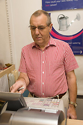 Volunteer worker using till in charity shop,
