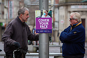 Two men have a face to face conversation next to a 'Cover your Face' sign in Folkestone town centre on the 27th of January 2021 in Folkestone, Kent, United Kingdom. Folkestone currently has one of the highest death rate in the country, some people are ignoring the guidelines and not covering their faces or standing 2 metres apart.