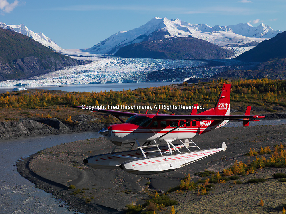 Rust's Flying Service Cessna 208 Caravan on floats flying past Colony Glacier, Lake George and Mount Muir, Alaska.