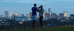 Primrose Hill, London, January 12th 2017. Dawn breaks over London, seen from Primrose Hill, as the South East of England braces itself for rain and possibly snow later in the day. PICTURED: A man and a woman exercise by boxing with each other against the backdrop of London's skyscrapers.