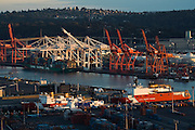 The loading cranes and cargo container ships at sunset at the Port of Seattle, Washington.