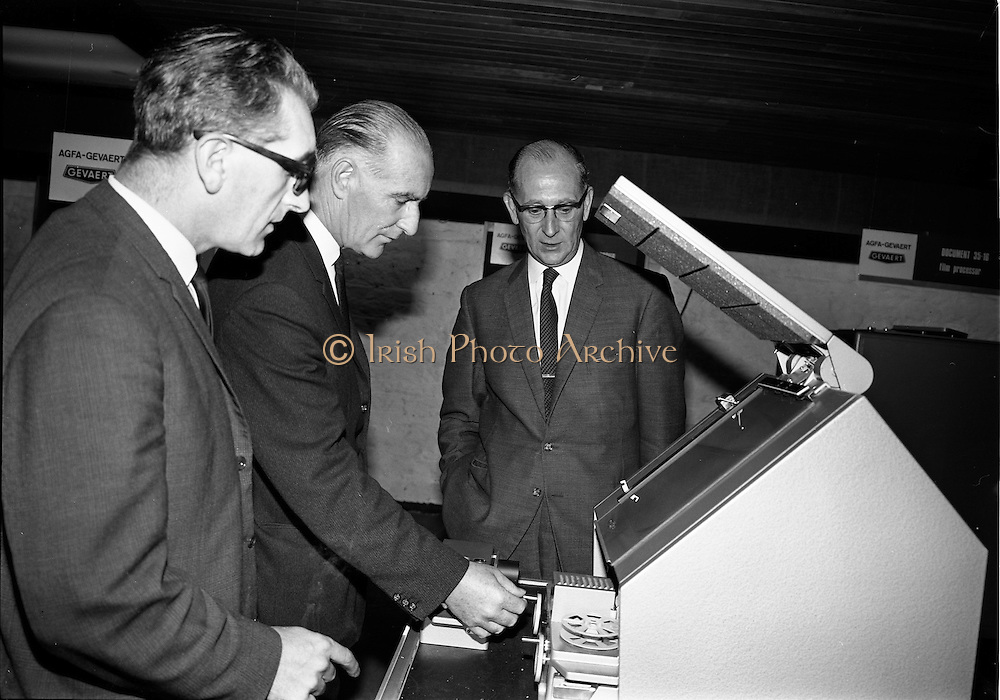 """19/09/1967<br /> 09/19/1967<br /> 19 September 1967<br /> Opening of Agfa-Gevaert exhibition at the Building Centre, Lower Baggot Street, Dublin. Exhibition """"Microfilms in the Space Age"""" demonstrating microfilming equipment and facilities, most of the equipment was exclusive to Agfa-Gevaert Limited. Pictured (l-r) are: Mr G.L. Latchtard, Kevin Street College of Technology;  Mr Hugh de Lacey, Kevin Street College of Technology and Mr Patrick Howard,General Manager, Agfa-Gevaert Ltd., viewing some of the equipment."""