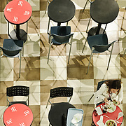 Two diners grab a bit to eat at the Union Station Food Hall. Shot taken from directly above, with a pattern of tiles, tables, and chairs.