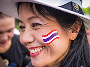 """09 JUNE 2013 - BANGKOK, THAILAND:  A woman with a Thai flag decal on her cheek participates in the White Mask anti-government protest in Bangkok. The White Mask protesters wear the Guy Fawkes mask popularized by the movie """"V for Vendetta"""" and the protest groups Anonymous and Occupy. Several hundred members of the White Mask movement gathered on the plaza in front of Central World, a large shopping complex at the Ratchaprasong Intersection in Bangkok, to protest against the government of Thai Prime Minister Yingluck Shinawatra. They say that her government is corrupt and is a """"puppet"""" of ousted (and exiled) former PM Thaksin Shinawatra. Thaksin is Yingluck's brother. She was elected in 2011 when her brother endorsed her.    PHOTO BY JACK KURTZ"""