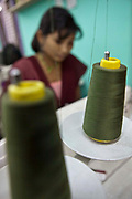 A Nepalese female factory worker operates a sewing machine making clothes in the Surijha Traders garment factory in Kathmandu, Nepal.  The garments produced in the factory are exported around the world. The factory works closely with the Friends of Needy Children organization in providing fair employment opportunities for young Nepalese men and women.