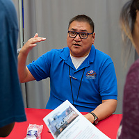 Anthony Billy, 42, of the Navajo Tribal Utility Agency discusses the opportunities with NTUA to students. The Career Fairwas held in the Wellness Center at the NTU campus in Crownpoint on Thursday.