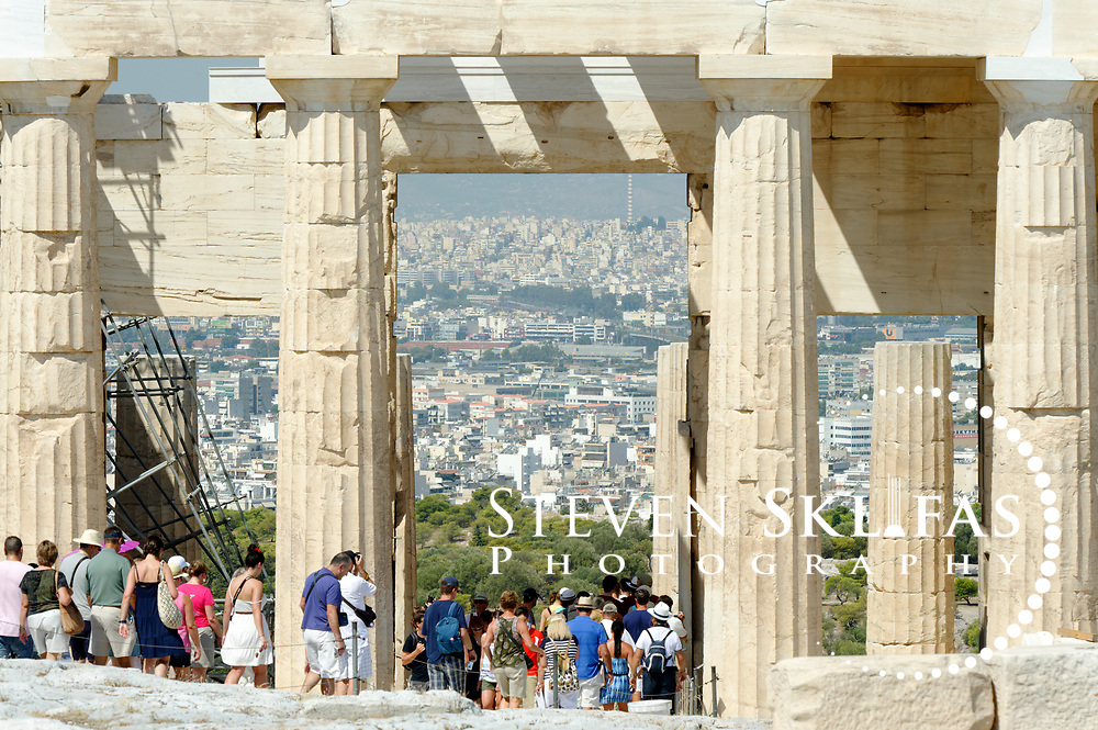 Acropolis. Athens. Greece. View of the people, tourists walking through the Propylaia, the grand entrance of the Acropolis. The propylaia was built between 437-432 BC as part of the monumental rebuilding and transformation of the Acropolis buildings during the time of Perikles. The Acropolis of Athens and its monuments are a UNESCO World Heritage Site.