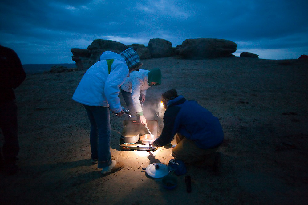 Campers cook dinner by headlamp on a camp stove at their wilderness campsite on BLM land near Factory Butte, Utah.