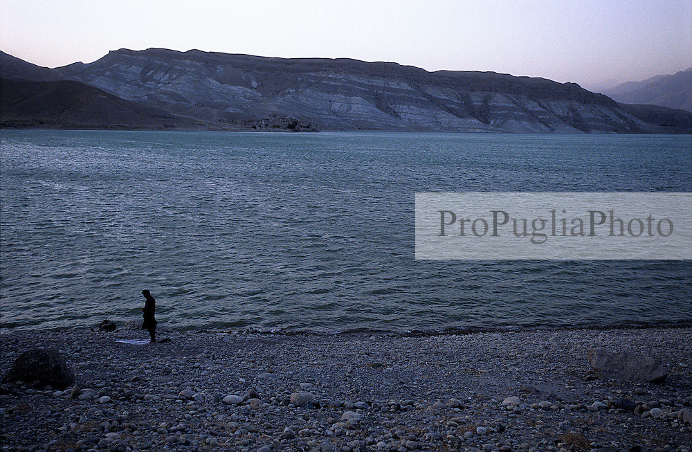 A taxi driver performing Salah on the river side, during his Torkham-Kabul trip