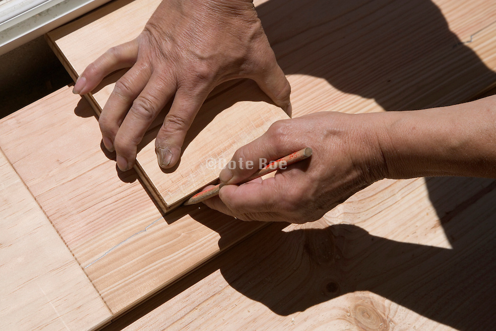 hand of woodworker measuring the last floor board