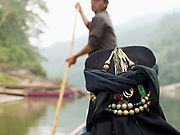 An Akha Nuquie ethnic minority woman travels in a local boat along the Nam Ou river to the her home in roadless village of Phou-Yot, three hours walk from the river, Phongsaly province, Lao PDR