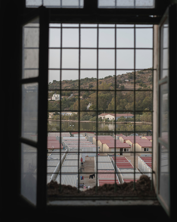 The First Reception Centre (Hot-Spot) of Leros, seen through a window the former Psychiatric Hospital. There are around 600 people living there. Since the July riots the camp has been split into different zones for the different ethnicities.  <br /> <br /> The Hot Spot in Lepida opened on the 26th of February 2016 in the grounds of the former Lepida psychiatric hospital.  At the beginning it served as a registration camp for refugees and migrants who were travelling to Europe through Greece but since the closure of the borders in March 2016 it serves as a permanent camp. People are allowed to go out, they have three meals a day, the prefabricated huts have a bathroom and are air-conditioned and compering to other refugee camps in Greece the conditions are bearable.