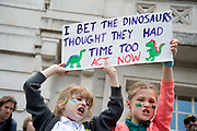 London Borough of Hackney, London. May 24th . Third strike by school students but Hackney primary school pupils went to the Town Hall after school to protest about the climate emergency. Two young girls hold a sign saying I bet the dinosaurs thought they had time too.