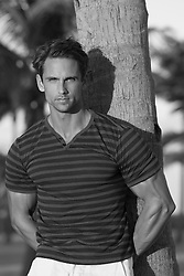 good looking man leaning against a tree at the beach in Miami, Florida