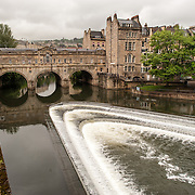 The historic Pulteney Bridge over the River Avon in central Bath, Somerset, United Kingdom. In the foreground man-made water level steps for the canal create whitewater.