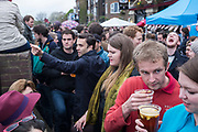 Spectators on the bank of the River Thames at Hammersmith during the annual Oxford and Cambridge Boat Race. London, UK.