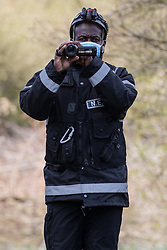Denham, UK. 6th April, 2021. An enforcement agent from the National Eviction Team working on behalf of HS2 Ltd uses a video camera to film a press photographer documenting tree felling for electricity pylon relocation works connected to the HS2 high-speed rail link alongside the Grand Union Canal in Denham Country Park.
