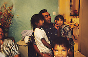The Baptiste family evening in their home. French Gitans, in the south of France, are full of spirit. They live as strong communal families with everyone looking after the children, living and breathing the rythmns of rhumba and flamenco music. Any chance to celebrate brings song and dance together with 'palmas' hand clapping. Some work the markets, others doing building, cleaning or maintenance work. Some live in municipal apartments others in caravans. They most often live within their own communities, distrustful of outsiders, and  experience problems of innercity life, and of racism. Roma people have suffered a history of racial persecution for centuries. Though mainly sedentary living in houses and apartments, they are still viewed from the outside as 'Les gens de voyage'. Many will holiday, take seasonal work or go to religious festival in their caravans, coming back to their house over for the rest of the year. Southern France