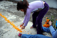 """MEXICO, Veracruz, Tantoyuca, Oct 27- Nov 4, 2009. A young girl lays out a """"cempasuchil"""" trail, so souls will know where to go, and the path to return when their time to visit is over. """"Xantolo,"""" the Nahuatl word for """"Santos,"""" or holy, marks a week-long period during which the whole Huasteca region of northern Veracruz state prepares for """"Dia de los Muertos,"""" the Day of the Dead. For children on the nights of October 31st and adults on November 1st, there is costumed dancing in the streets, and a carnival atmosphere, while Mexican families also honor the yearly return of the souls of their relatives at home and in the graveyards, with flower-bedecked altars and the foods their loved ones preferred in life. Photographs for HOY by Jay Dunn."""