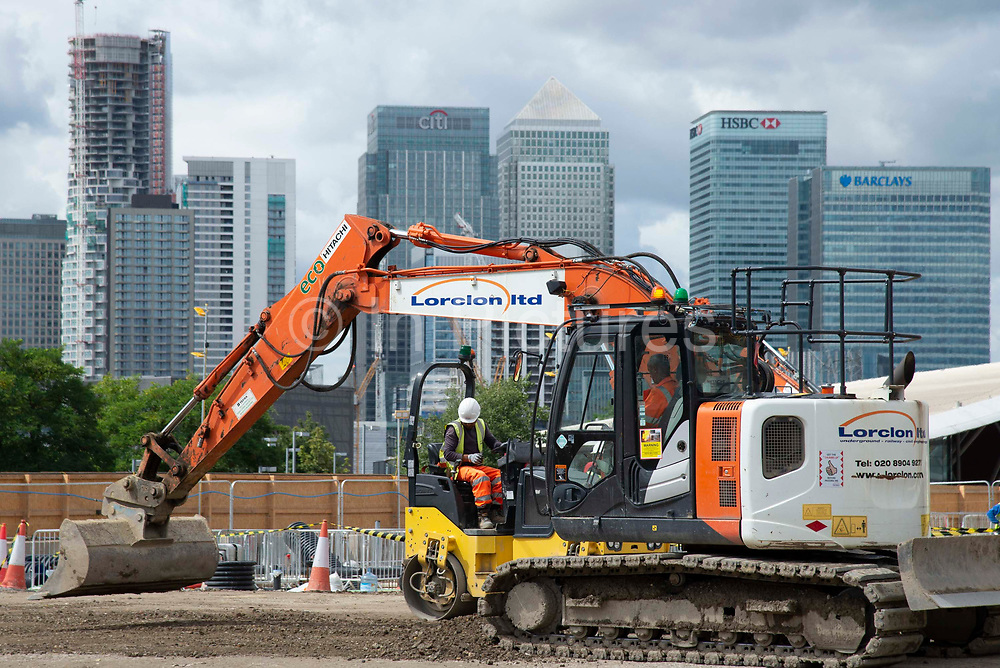 Canary Wharf is seen in the background as a man drives a digger on the  Design District construction site in Greenwich Peninsula in London, United Kingdom on 15th August , 2019. Scheduled to fully open in 2020, developers Knight Dragon Developments Ltd aim to deliver 15,000 new homes. 13,000 new jobs. 7 new neighbourhoods.