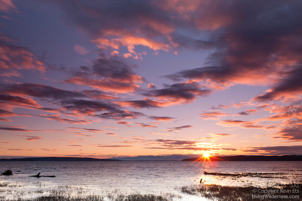 The sun sets behind the Olympic Mountains, coloring the sky above Skagit Bay in this view from Fir Island, Washington. Camano Island is visible on the left; Whidbey Island is visible on the right.