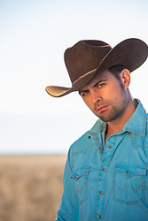 handsome rugged cowboy with green eyes outdoors