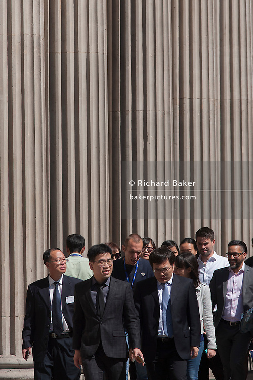 Visiting Chinese businessmen walk beneath the pillars of the Bank of England in Threadneedle Street, City of London, UK.