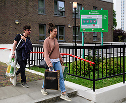 © Licensed to London News Pictures. 24/06/2017. London, UK. A young couple being evacuated from the Burnham block on the Chalcots Estate in Camden after it failed a fire inspection because of combustable cladding. More than 700 flats in tower blocks on an estate in the Swiss Cottage area of north-west London are being evacuated because of fire safety concerns. Photo credit: Ben Cawthra/LNP