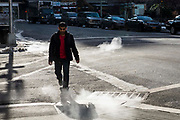 A man crosses a road passing steam coming out of the  air vents coming out of the road in Manhattan, New York City, New York, United States of America.