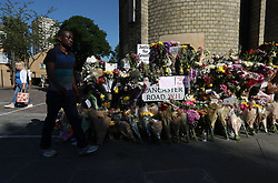 People walk past floral tributes outside Notting Hill Methodist Church, near to the Grenfell Tower in west London after a fire engulfed the 24-storey building on Wednesday morning.