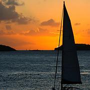 A sailboat sails quietly toward a beautiful Caribbean sunset in the US Virgin Islands.