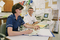Male and female nurses working at desk in hospital; making notes and smiling,