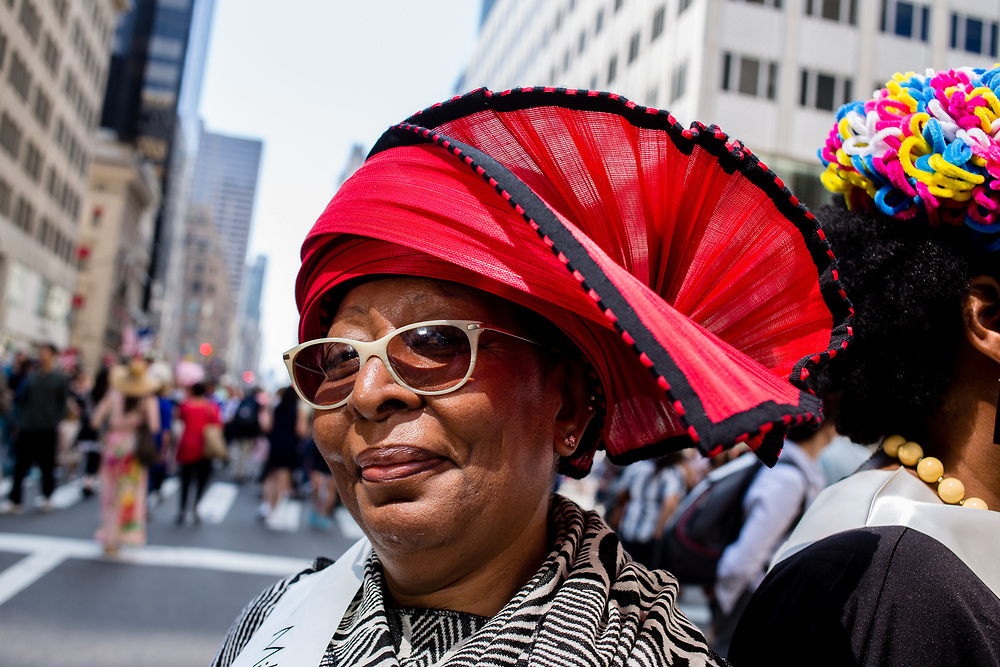 New York, NY - April 16, 2017. A woman from The Milliners Guild wearing a red and black hat at New York's annual Easter Bonnet Parade and Festival on Fifth Avenue.