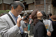 man making notes on his electronic gadget during a tourist tour in the Shugakuin Imperial villa garden Tokyo Japan