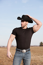 cowboy with large biceps outdoors