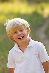 little blond boy smiling outdoors