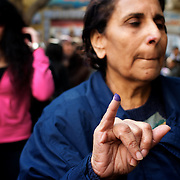An egyptian woman shows the ink in his finger after voting at Darode El Farag secondary school in Cairo's Shubra district.